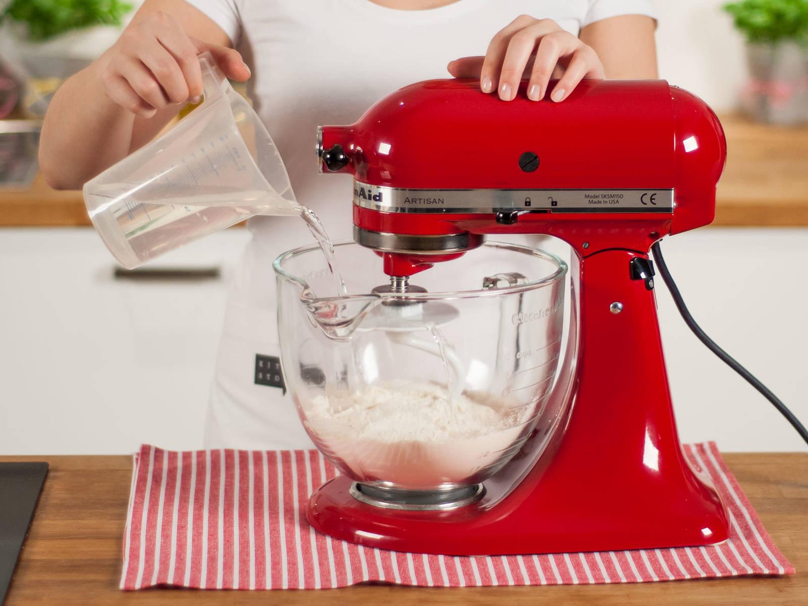 将面粉放入立式搅拌机或手持搅拌机中,加少许盐,然后加入水,搅拌5-7分钟,至面团顺滑。