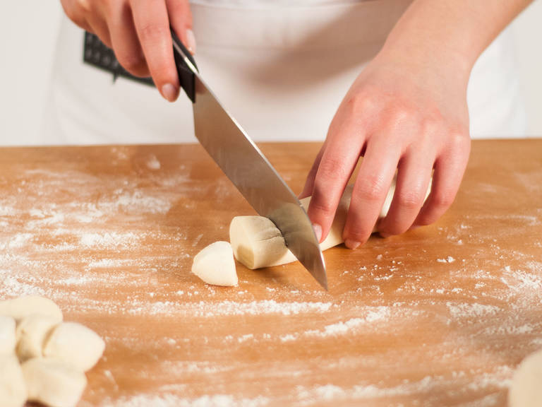 On a lightly floured work surface, knead the dough. Using a sharp knife, separate into 4 equally sized portions. Halve quarters and roll each portion into a small log. Cut each log into 8 walnut-sized pieces.