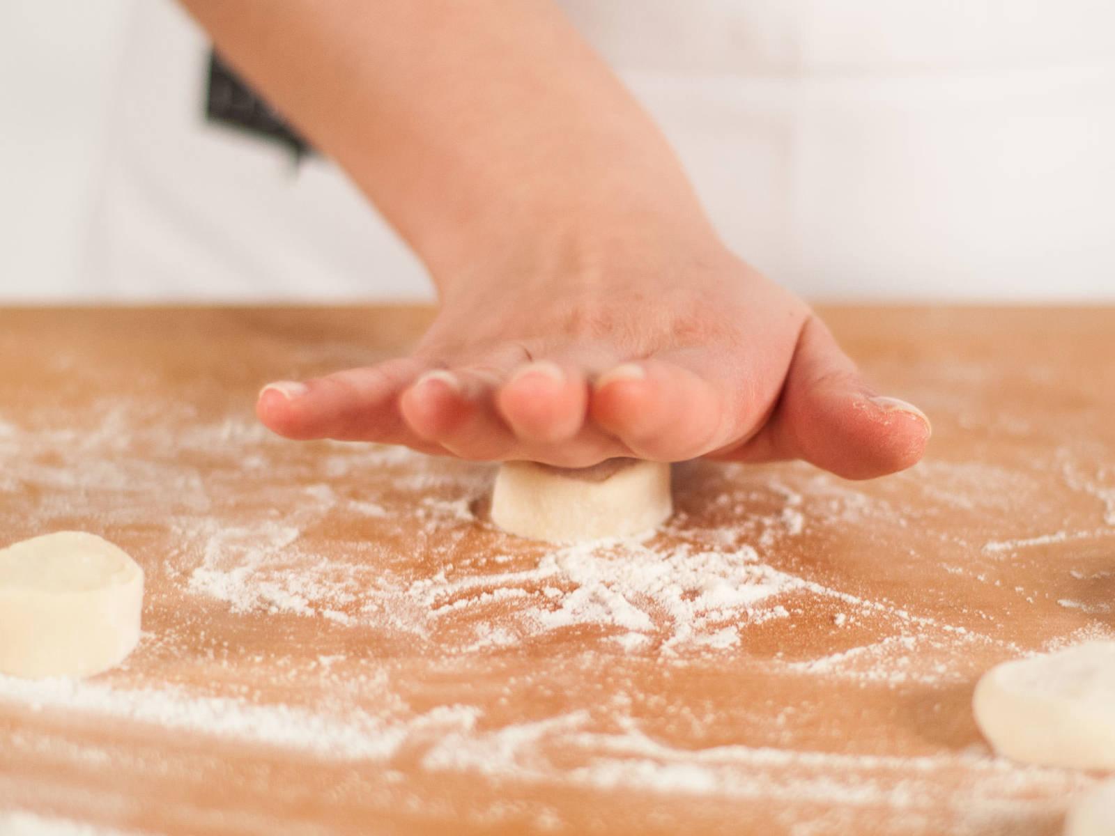 再撒些面粉,轻揉片刻使其近似圆形。然后将小面团分别按成圆饼。