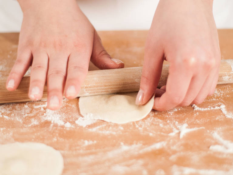 With a small rolling pin, roll each piece into a circle in the size of a small hand palm. To avoid tearing, make sure that the center of the dumpling is slightly thicker.