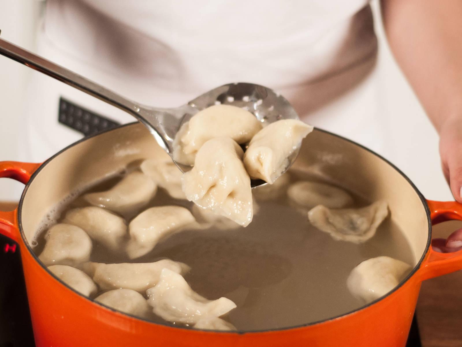 待第4次加入冷水后立即熄火,用漏勺将饺子捞入深盘中,倒掉盘中残留的水分。继续煮剩余的饺子。