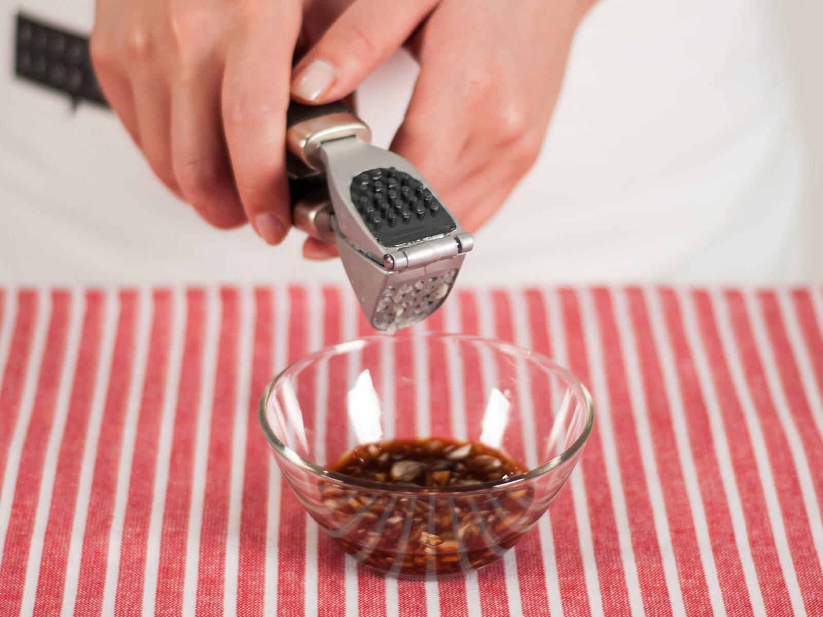 蒜酱汁的制作:用压蒜器将蒜压入小碗,加入醋和糖搅拌均匀。 用饺子配蒜酱汁趁热享用吧!