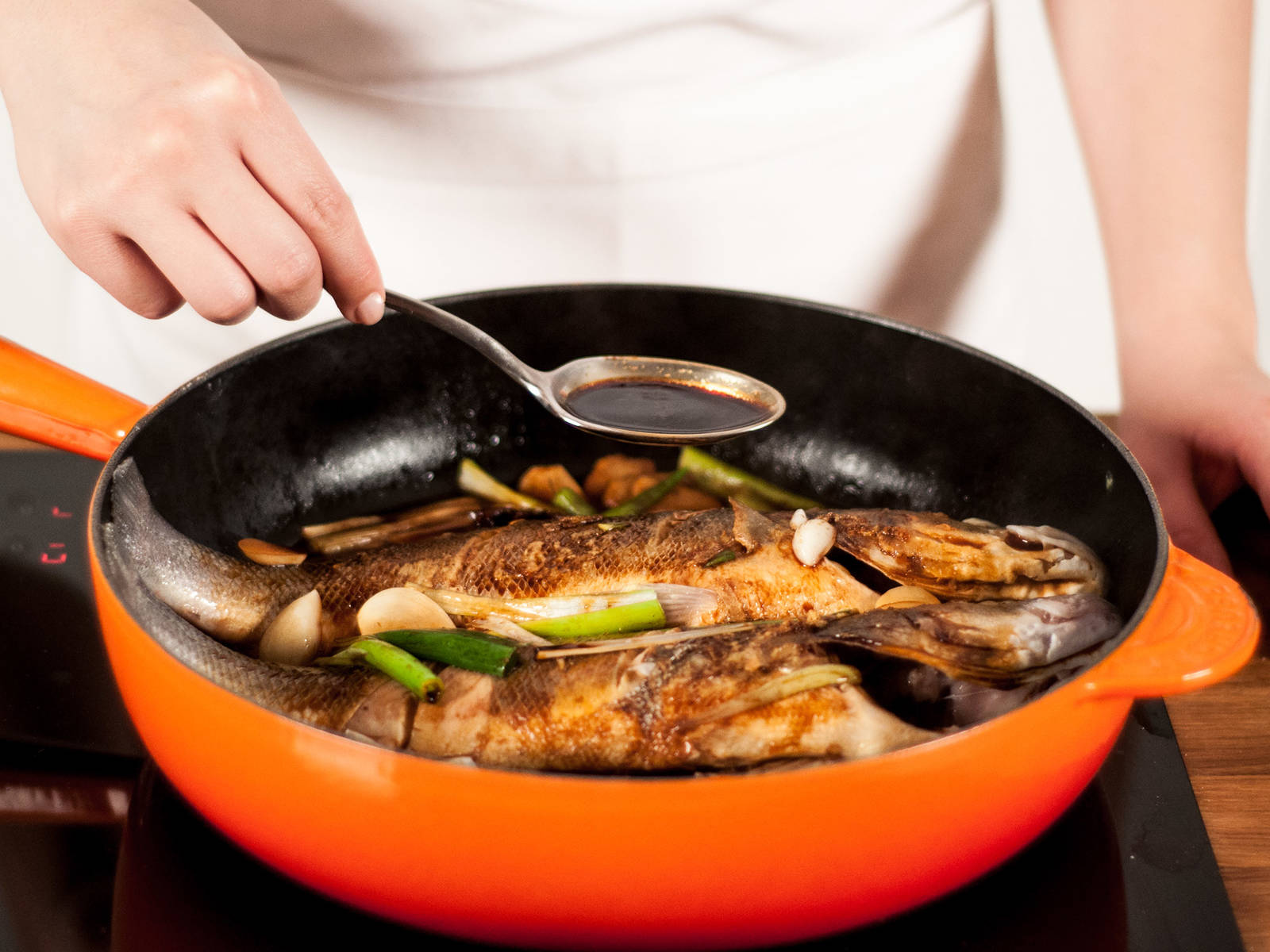 在煎锅中加入水,用勺子将汤汁淋在鱼上。加盖,大火煮至汤汁沸腾,转中小火继续煮20-23分钟。