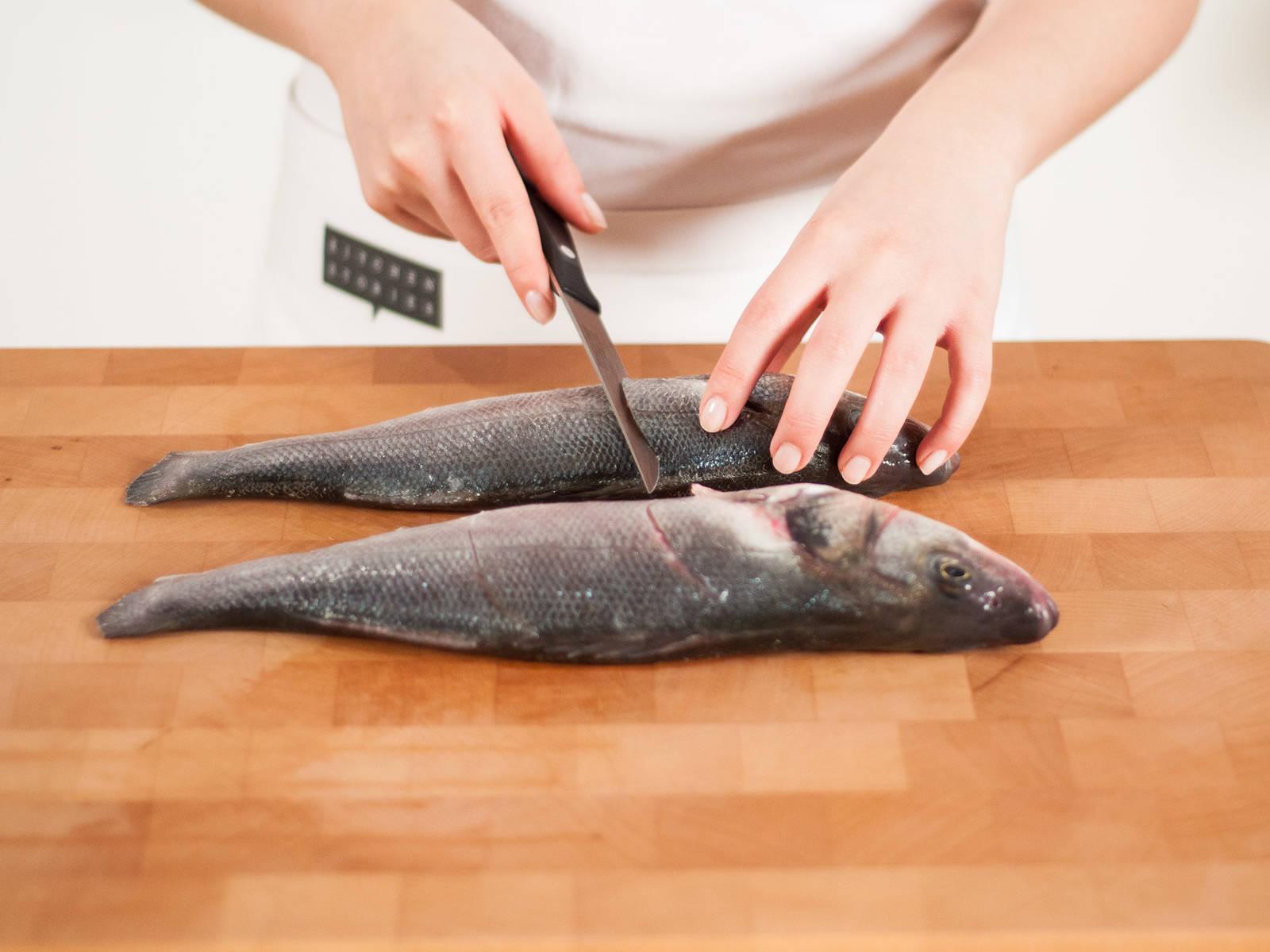 将鱼放在砧板上,在每条鱼的两面各划两刀。