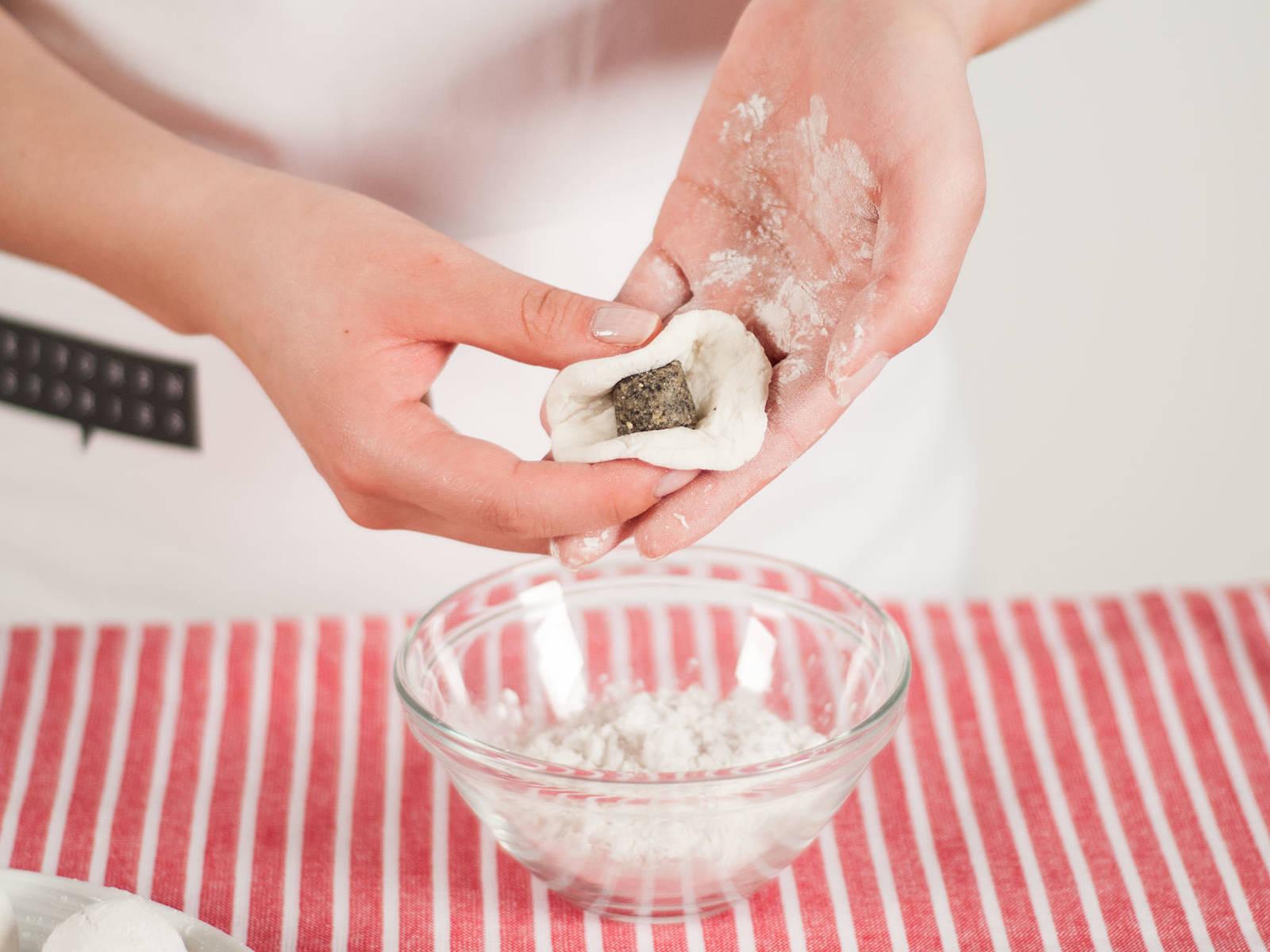 Hände leicht bemehlen. Kleine Portion Teig nehmen (ca. 1 EL) und einen kleinen Kreis formen. Füllung in der Mitte platzieren, mit Teig umwickeln und zu kleinen Bällchen rollen. Mit Klebreismehl benetzen.