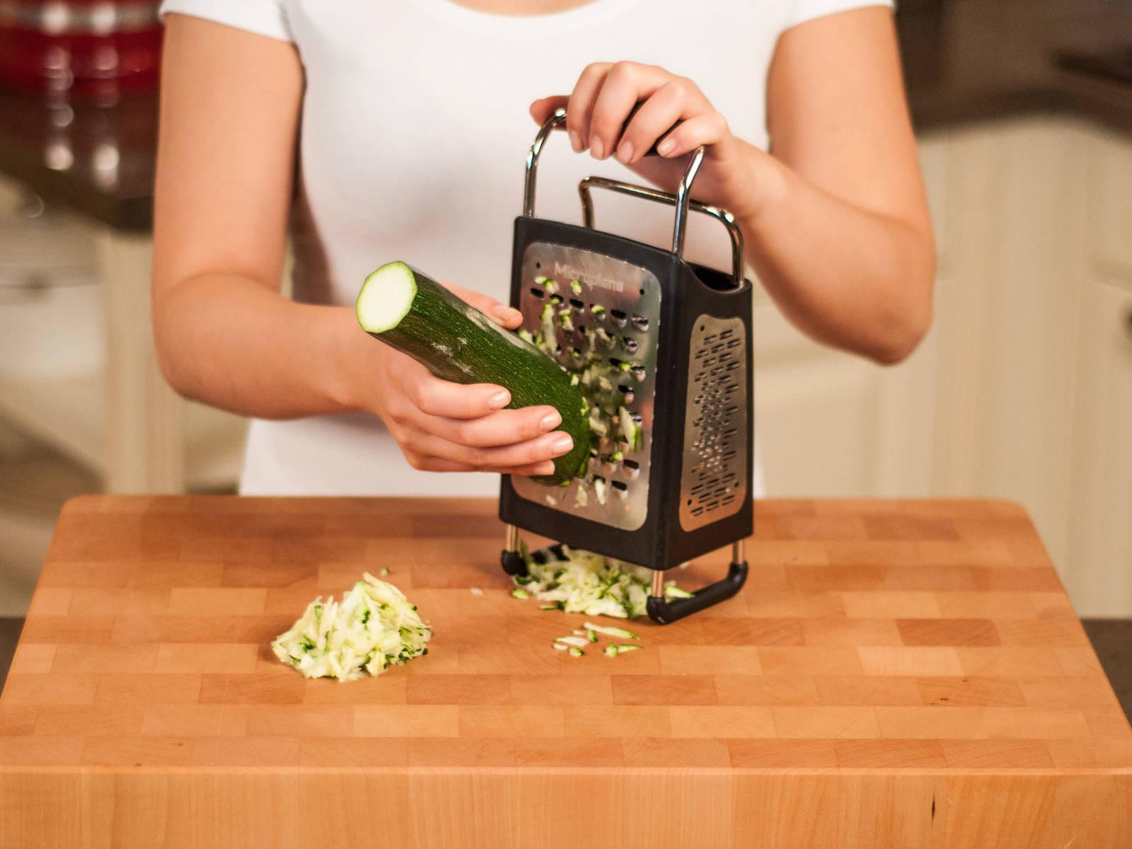 Backofen auf 180°C vorheizen. Enden der Zucchini abschneiden und Zucchini grob reiben. Dazu die großen Löcher der Vierkantreibe benutzen.
