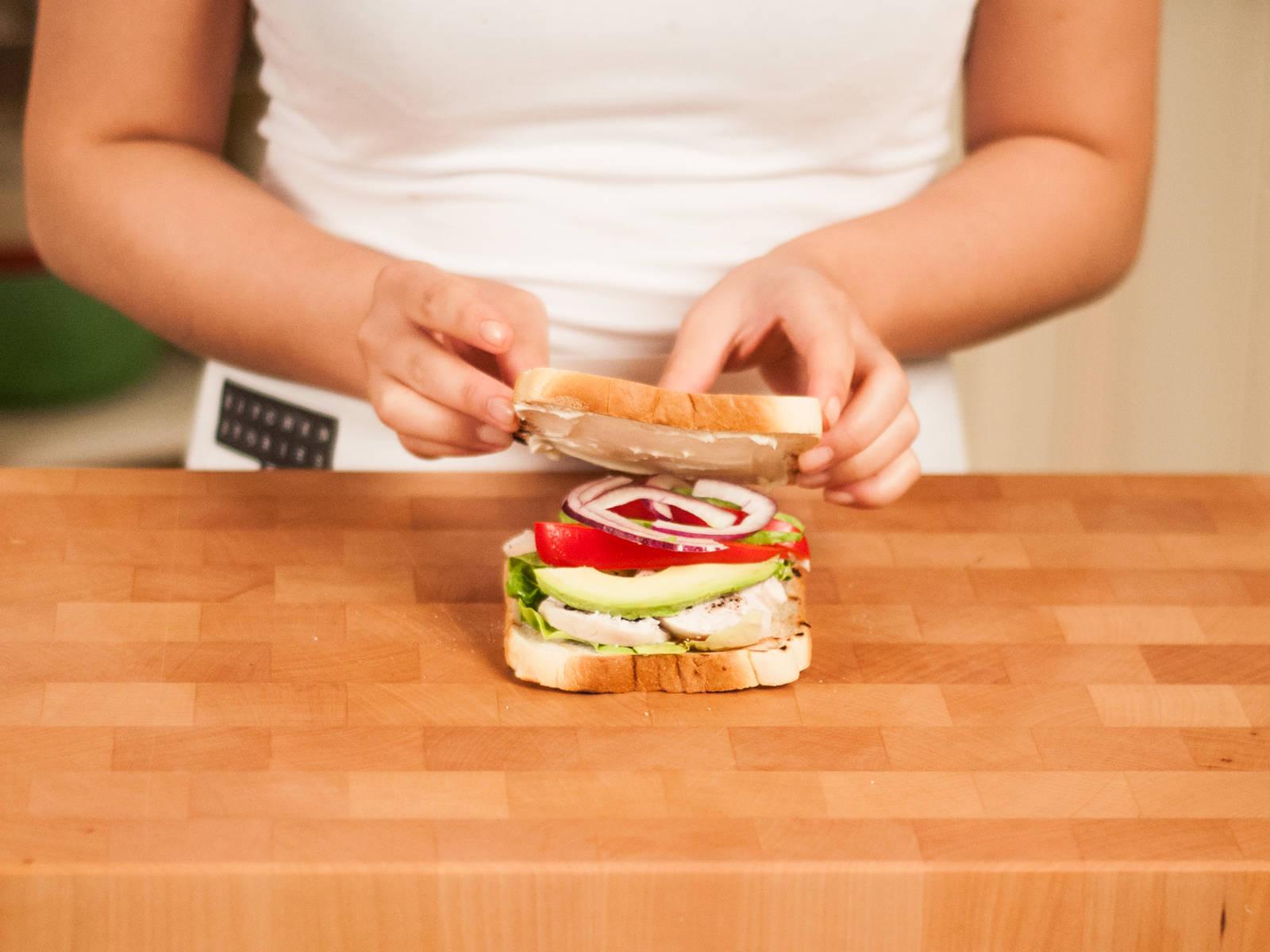 Hühnerbrust in Streifen schneiden. Auf einer Toastbrotscheibe Salat, Hühnchen, Avocado, Paprika und Zwiebel schichten. Nach Geschmack mit Salz und Pfeffer würzen. Die zweite Toastscheibe großzügig mit Frischkäse bestreichen und auf die andere, belegte Toasthälfte legen. Sandwich diagonal halbieren und mit süßer Chilisoße servieren.