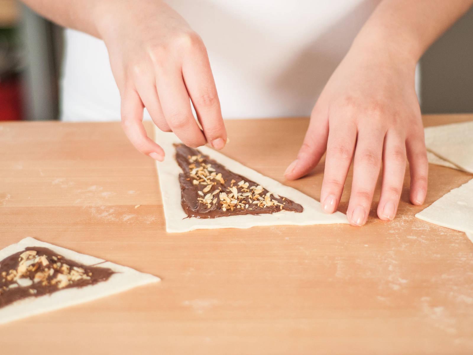 Sprinkle almonds on top of hazelnut spread.