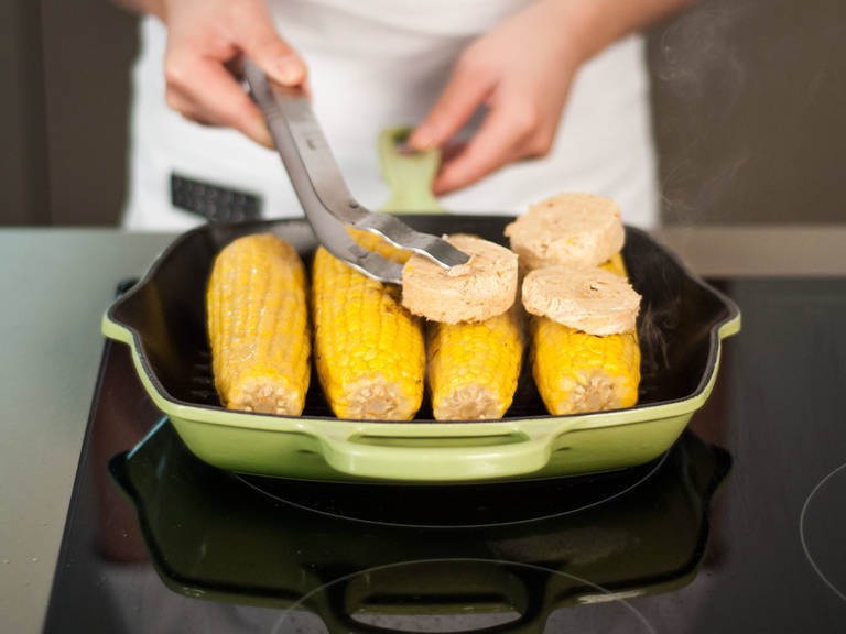 Heat some vegetable oil in a grill pan and sauté corn over medium heat for approx. 4 – 5 min. until slightly caramelized. Cut butter into medallions, place on top of corn, and continue to sauté for approx. 8 – 10 min. until corn is lightly charred and butter is golden brown. Transfer corn to plate and pour over remaining butter.