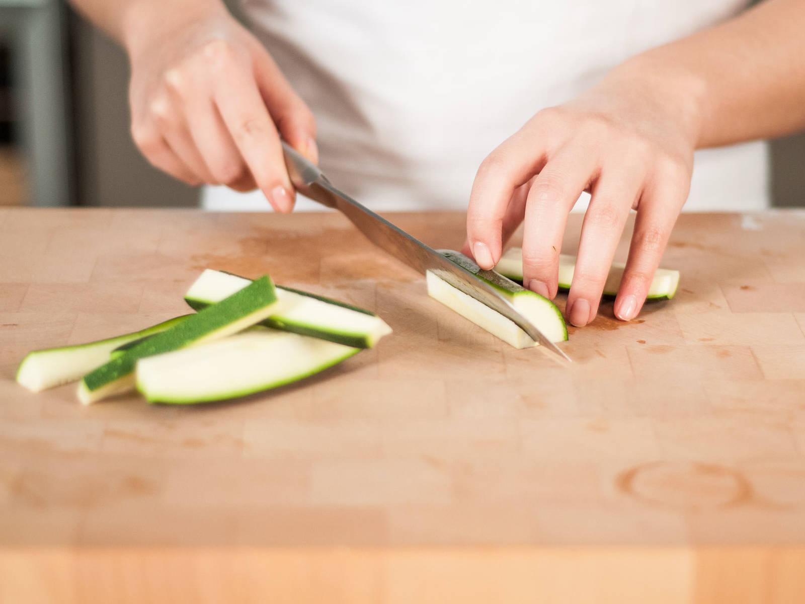 将西葫芦对半切开,先纵向切成四瓣,斜切去籽,再切成条状。