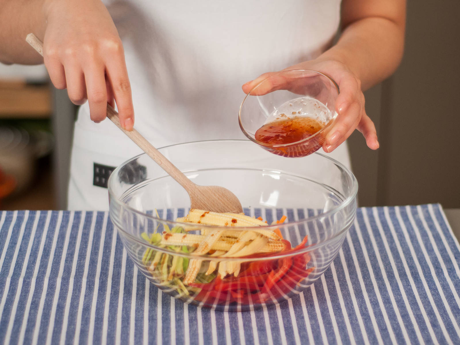 In a large bowl, mix sliced carrots, leek, bell pepper, and baby corn with sweet chili sauce and soy sauce.