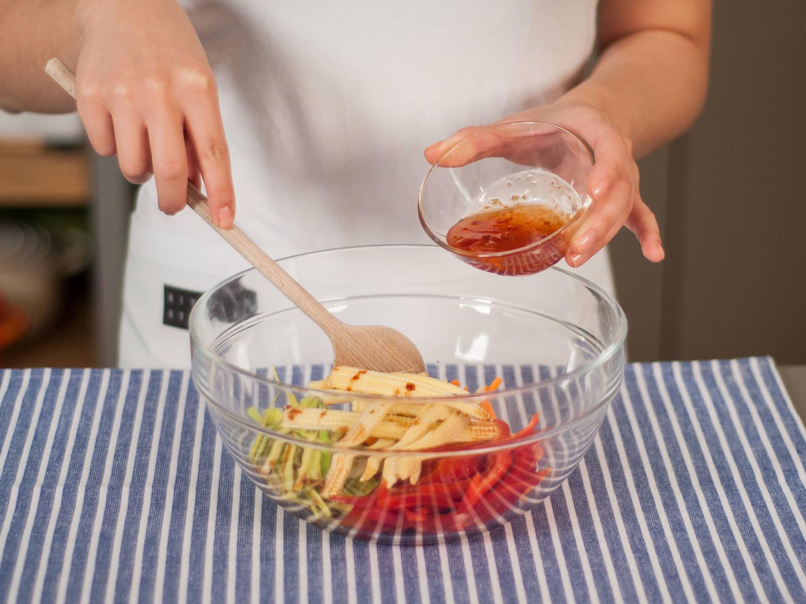 将切丝的胡萝卜、韭葱、甜椒和玉米笋放入大碗中,加入甜辣酱和酱油。