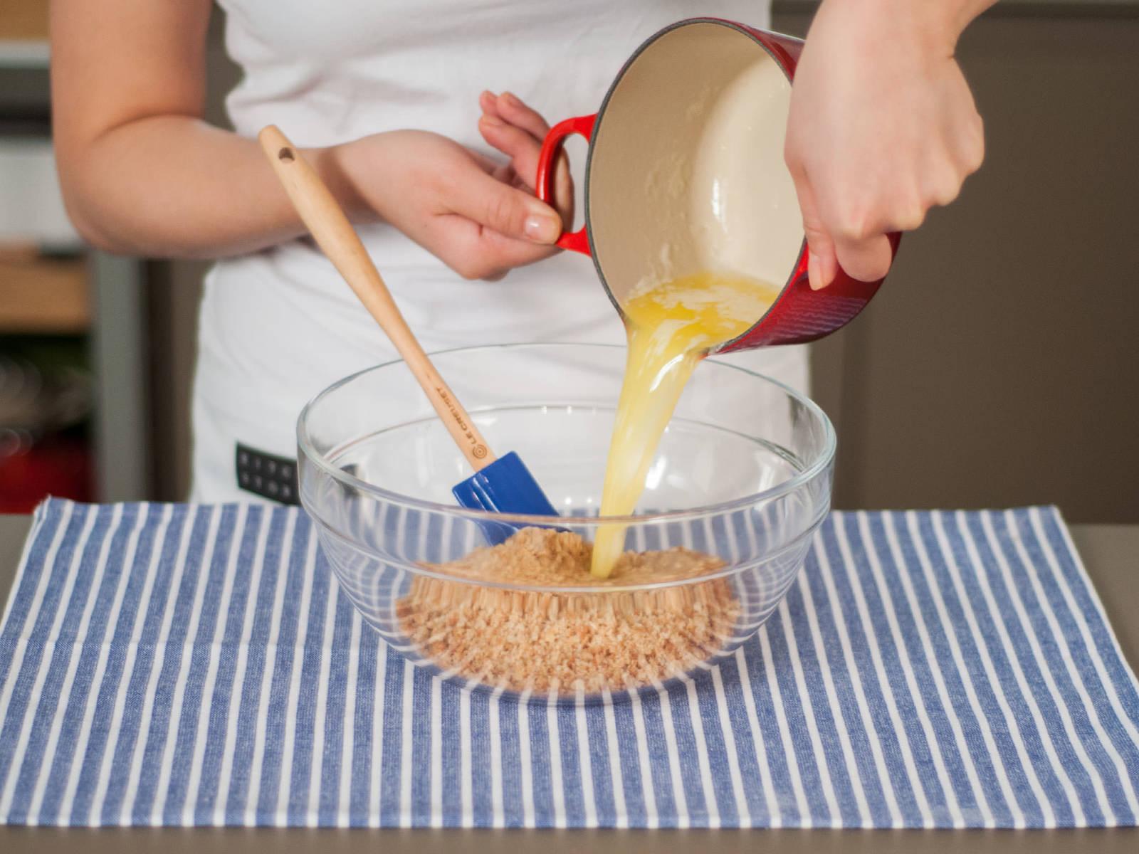 用中低温将黄油在小锅中融化,然后倒入放有饼干屑的大碗中,搅拌均匀。