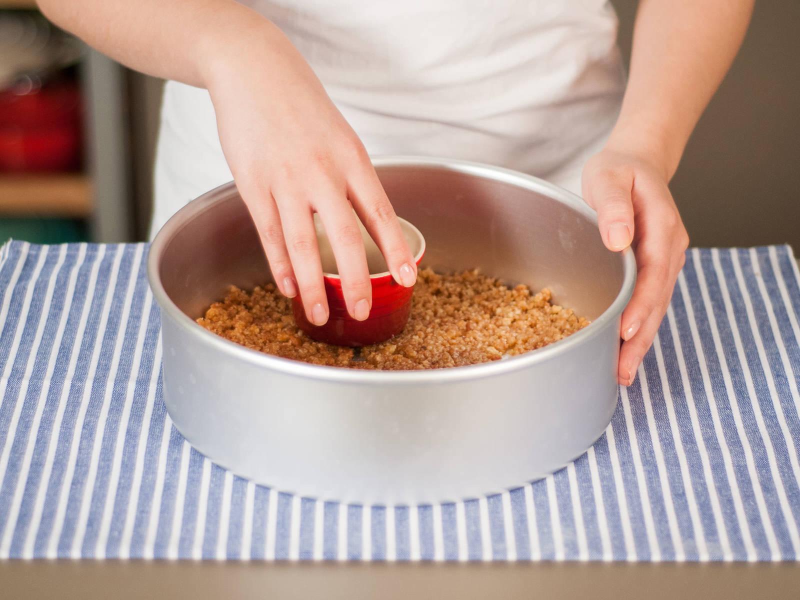 将饼干屑混合物铺在烤模底部,压实。
