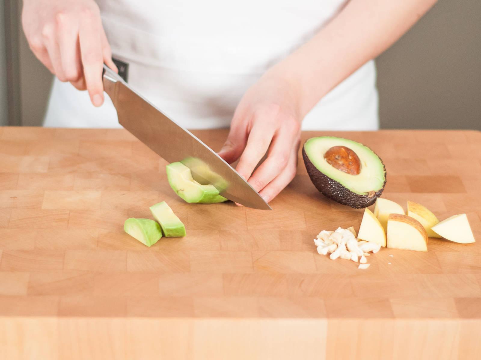将苹果、黄瓜、腰果和鳄梨粗略切碎。