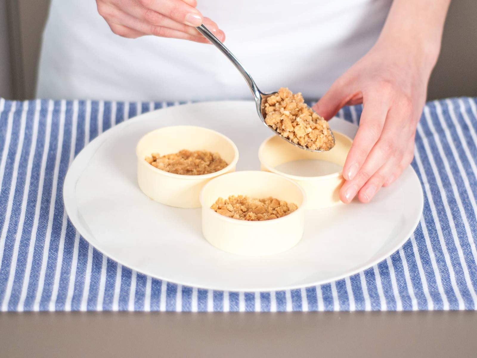 Keksmischung mit einem Löffel in die Backformen geben und leicht andrücken, um den Boden zu formen.