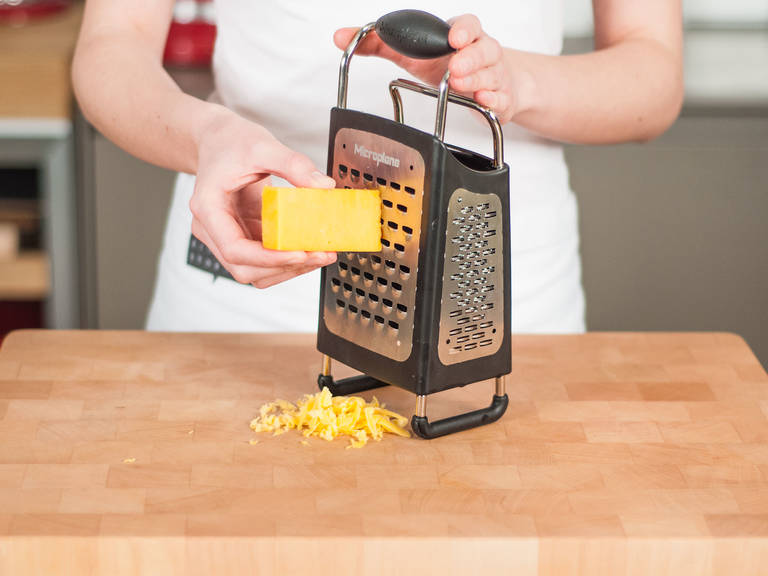 Using a box grater, roughly grate cheese.