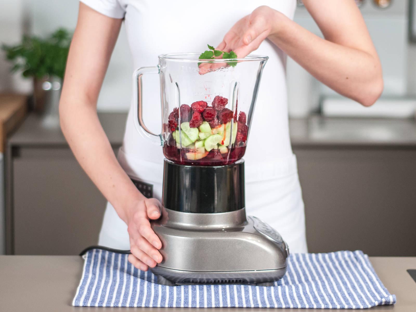 将黄瓜、红甜菜、冰冻覆盆子、龙舌兰糖浆与水加入搅拌机中。摘取薄荷叶,加入搅拌机中。