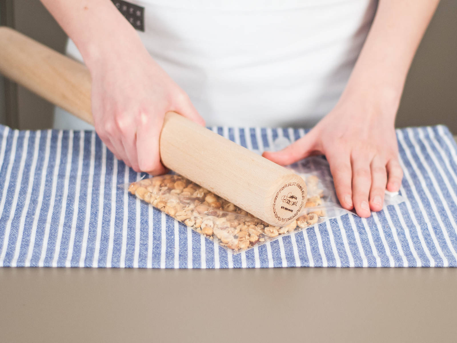 预热烤箱至180摄氏度。将榛子放入冷冻袋中,用擀面杖碾碎。