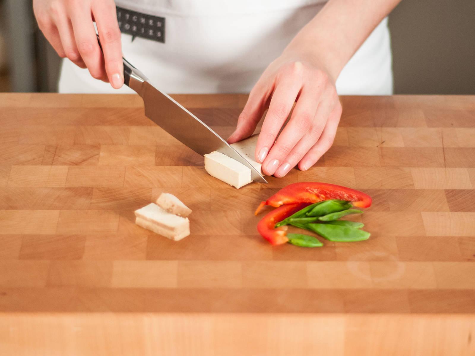 Zuckerschoten mit einem diagonalen Schnitt halbieren. Paprika in feine Streifen schneiden. Tofu längs in gleichmäßige Stücke schneiden.