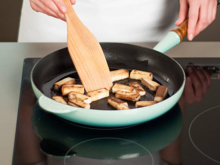在煎锅中用中温加热少许植物油,将豆腐每面煎3–5分钟,直至表面微干且酥脆。