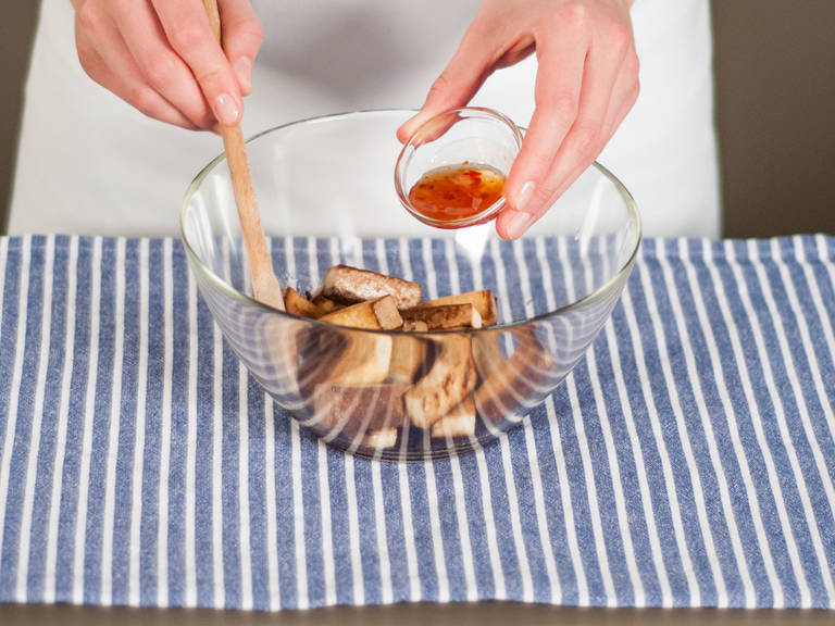 将豆腐放入碗中,加入酱油与甜辣酱,并搅拌使豆腐片均匀裹上酱汁。置于一旁备用。