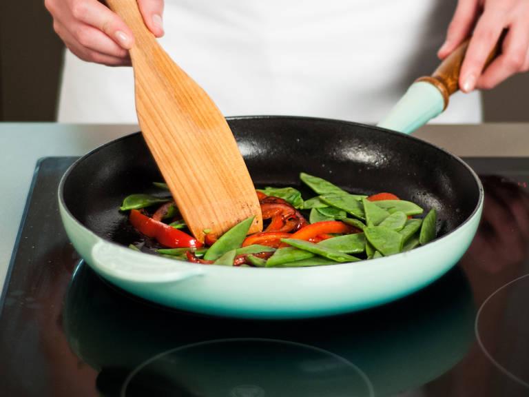 在煎锅中加热更多植物油,用中温翻炒荷兰豆和灯笼椒5-7分钟,直至表面微干,加盐和胡椒粉调味。