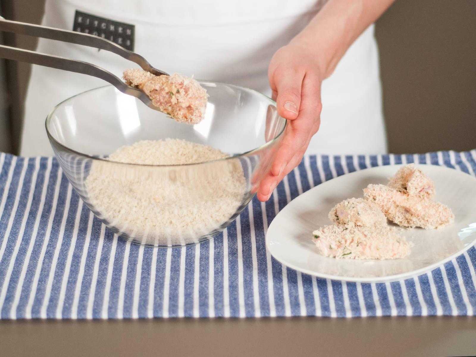 将鸡翅放入盛有面包屑的大碗中,用夹子翻动鸡翅,使鸡翅各面均匀裹上面包屑。
