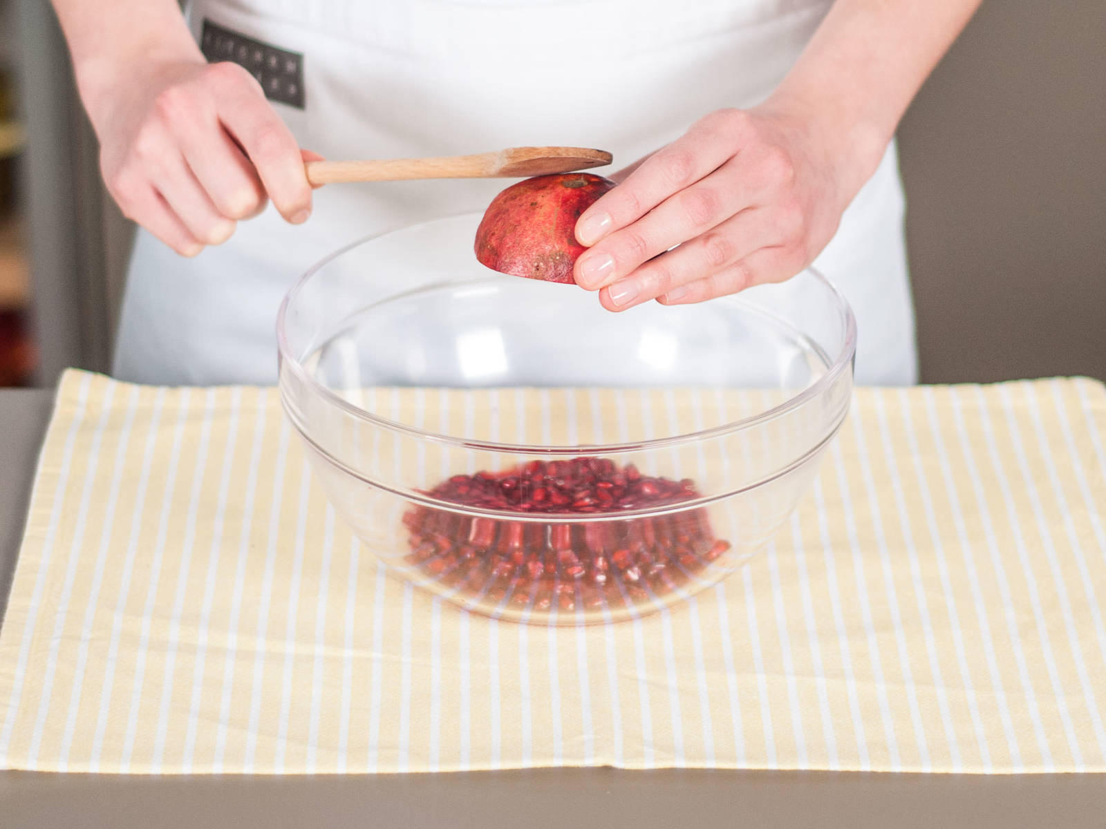 Remove pomegranate seeds and add to large bowl. For easy seed removal, first roll pomegranate on counter to loosen seeds, cut in half, and hold each half over the bowl while tapping firmly with wooden spoon.