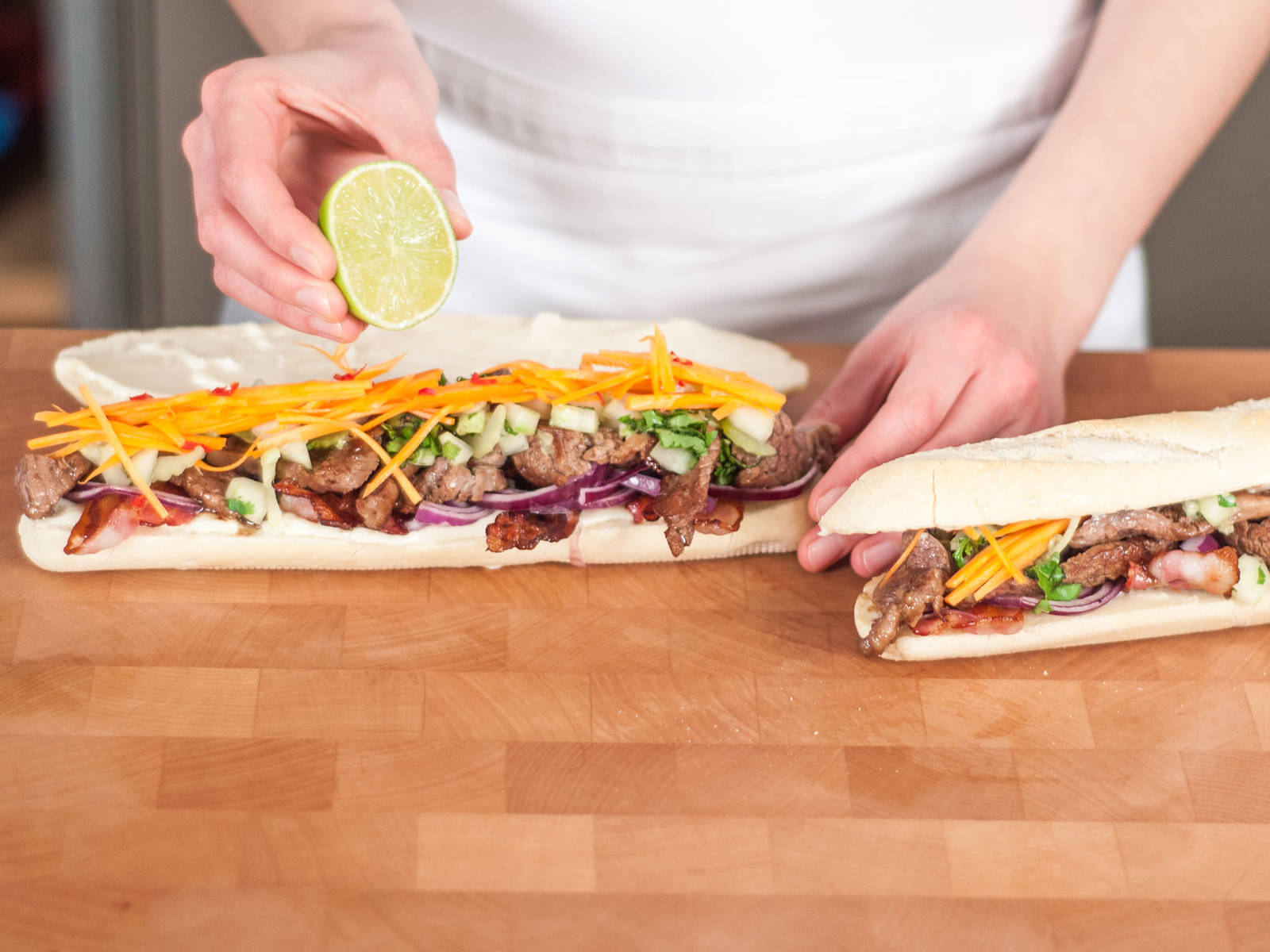 Cut baguette lengthwise, but not all the way through. Spread top and bottom layer of baguette with mayonnaise. Layer with bacon, beef, vegetables, and herbs. Garnish with remainder of chopped cilantro and top it off with a drizzle of lime juice. Enjoy!