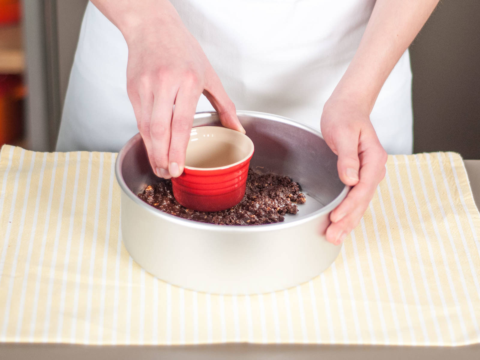 Add cookie crumb mixture to a round baking form and press firmly into bottom of baking form.