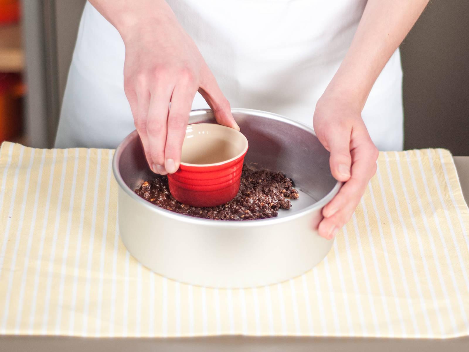 Kekskrümelmischung in eine runde Backform geben und sorgfältig an den Boden der Backform drücken.