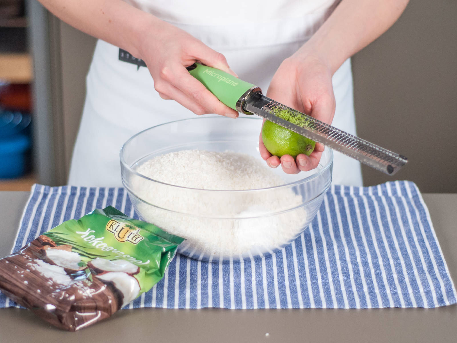 擦取一部分酸橙皮碎。向大碗中加入面粉、泡打粉、椰蓉与酸橙皮碎,并搅拌均匀。