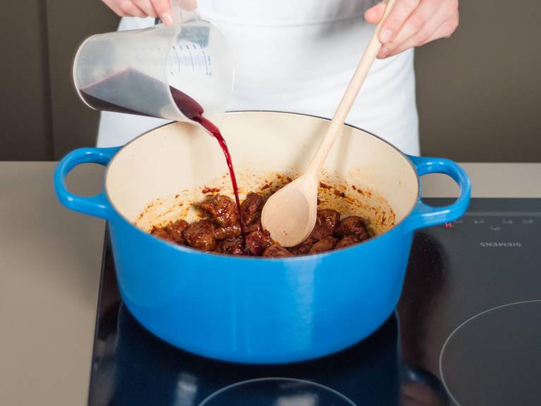 Pflanzenöl in einem großen Topf erhitzen. Rindfleisch darin bei mittlerer Hitze ca. 4 – 6 Min. braun anbraten. Tomatenmark hinzufügen und mit anrösten. Dann mit Rotwein ablöschen und einkochen, bis ein Drittel der Flüssigkeit verdampft ist.
