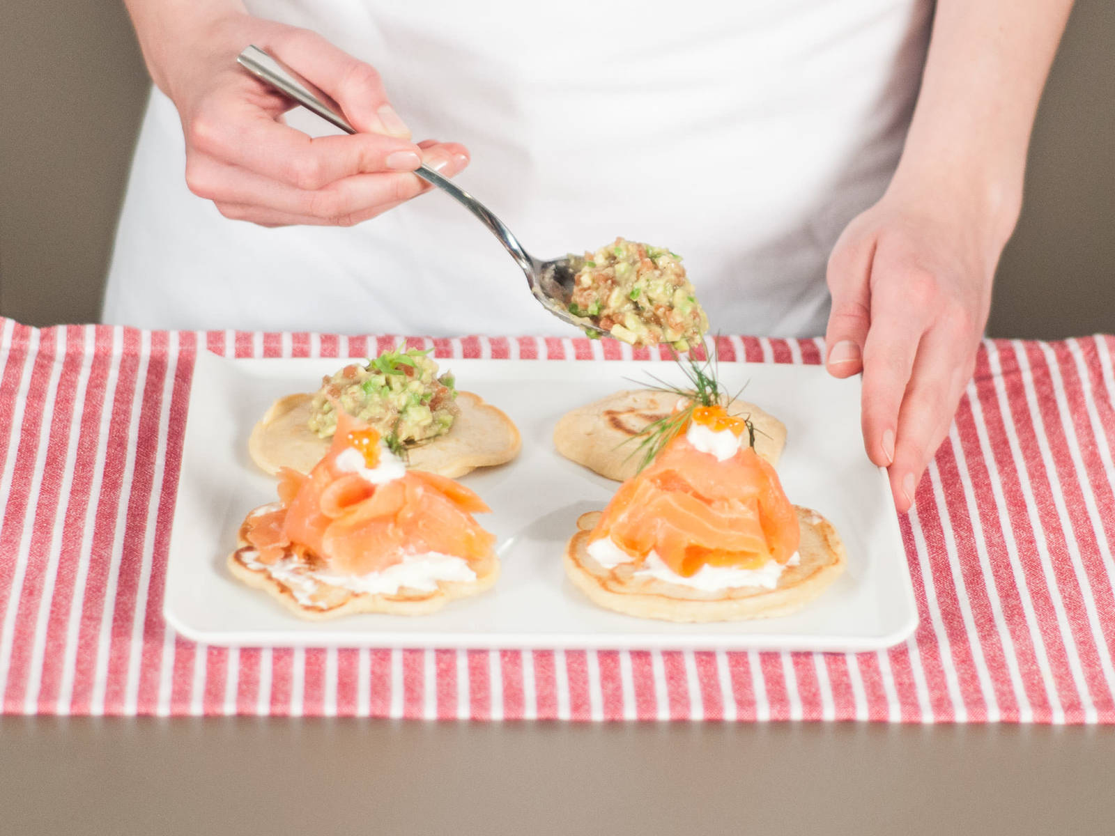 将奶油奶酪酱放在其中两个薄饼上,然后放上片好的三文鱼,饰以鱼子酱。将鳄梨番茄鞑靼放在另外两个薄饼上,根据需要饰以小茴香。可作为开胃菜、早餐或小吃享用。