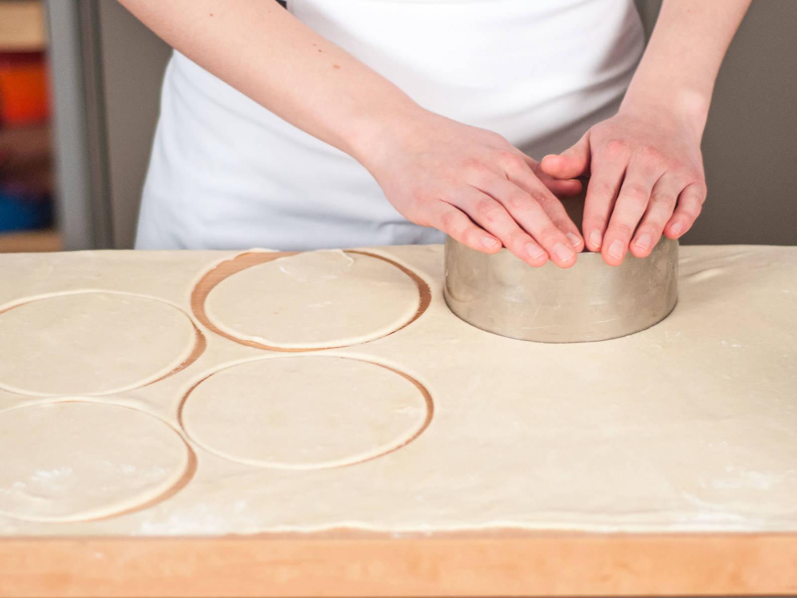 将烤箱预热至180摄氏度。在工作台上撒少许面粉,用擀面杖将面团擀成薄片。用刀将面皮切成圆形。