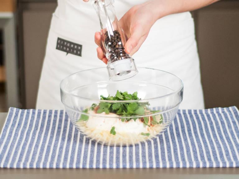 Korianderblätter abzupfen und grob hacken. Dann in einer großen Schüssel die Hälfte des Käses, Crème fraîche und Koriander vermengen. Mit Paprikapulver, Salz und Pfeffer abschmecken.