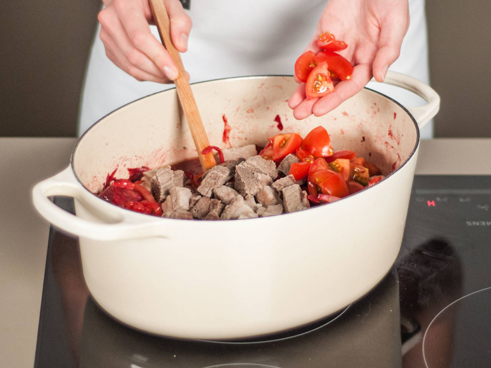 向锅中加入肉、多香果与番茄,并充分搅拌。
