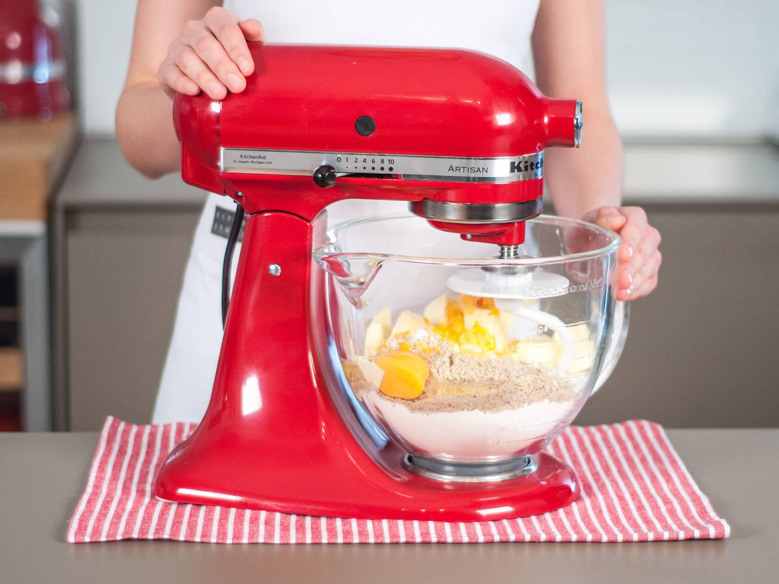 外皮的制作:将黄油、糖粉、杏仁粉、面粉、盐、鸡蛋、部分柠檬皮碎与部分橙子皮碎混合,并搅拌成光滑的面团。