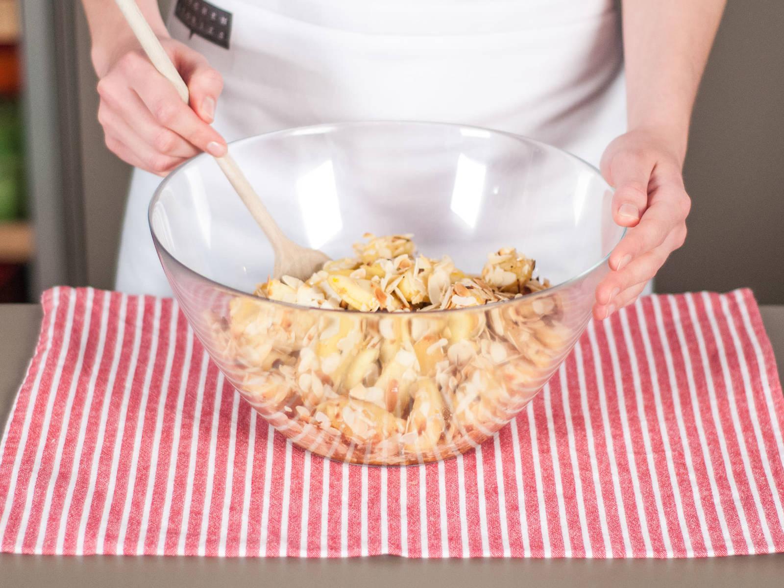 Apfelfüllung mit gerösteten Mandeln in einer großen Schüssel vermengen.