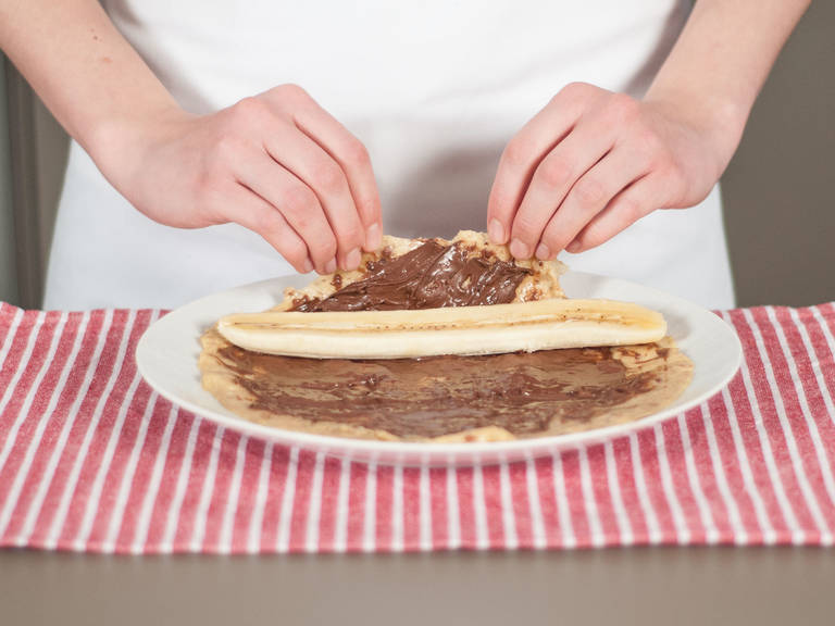 Spread a thin layer of hazelnut spread over each pancake. Place a banana slice on top and roll the pancake up. Enjoy with confectioner's sugar, if desired.