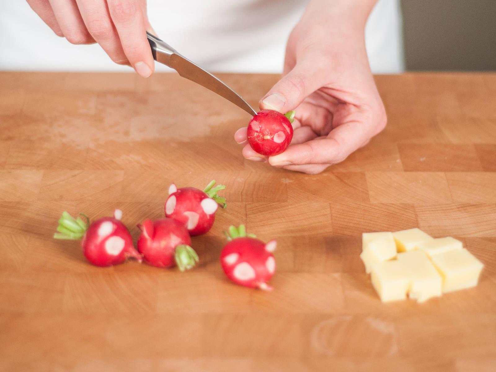 奶酪切块。樱桃萝卜清洗干净即可,无需去蒂,以便做出小老鼠造型。借助一把锋利的小刀雕出眼睛部分,在眼睛上方划出两道缝隙,将雕刻眼睛时切下的萝卜分别插在两道缝隙中,做成耳朵。