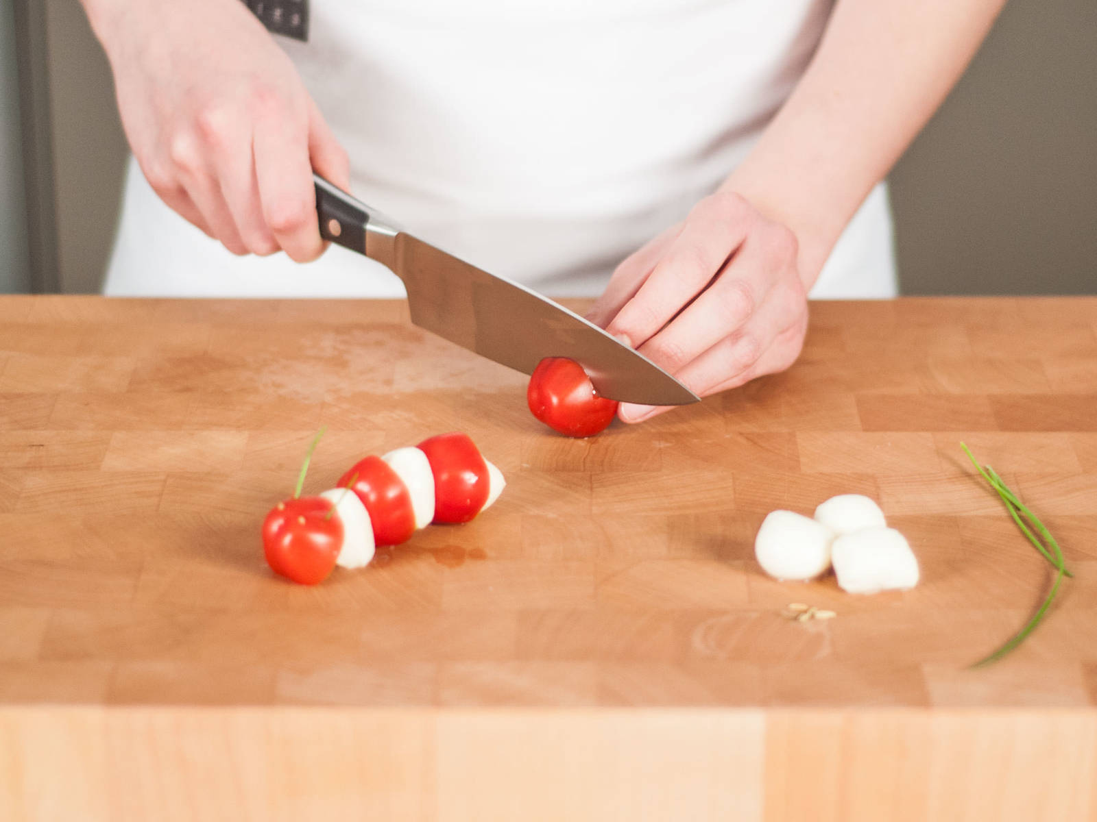 For the caterpillars, halve mozzarella balls and cherry tomatoes. For the head, slice pieces of chives, poke small holes in the head end, and stick chives into holes for antennas. Use a toothpick to poke holes for eyes. Arrange on a toothpick, alternating the mozzarella and tomato pieces.