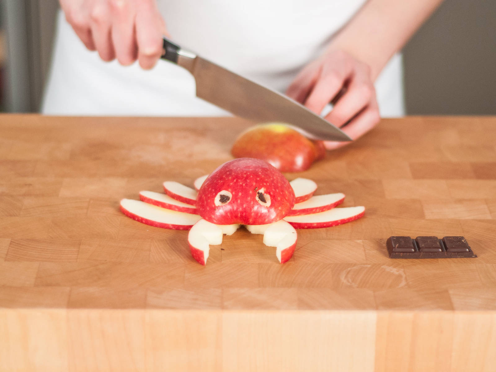 For the crab, halve one apple and cut out the core. Core and cut the other half into thin slices for legs, and cut serrated edges into two slices for the claws. Carve out small holes for the eyes, and stick small pieces of chocolate into the holes. If desired, use toothpicks to hold everything together.