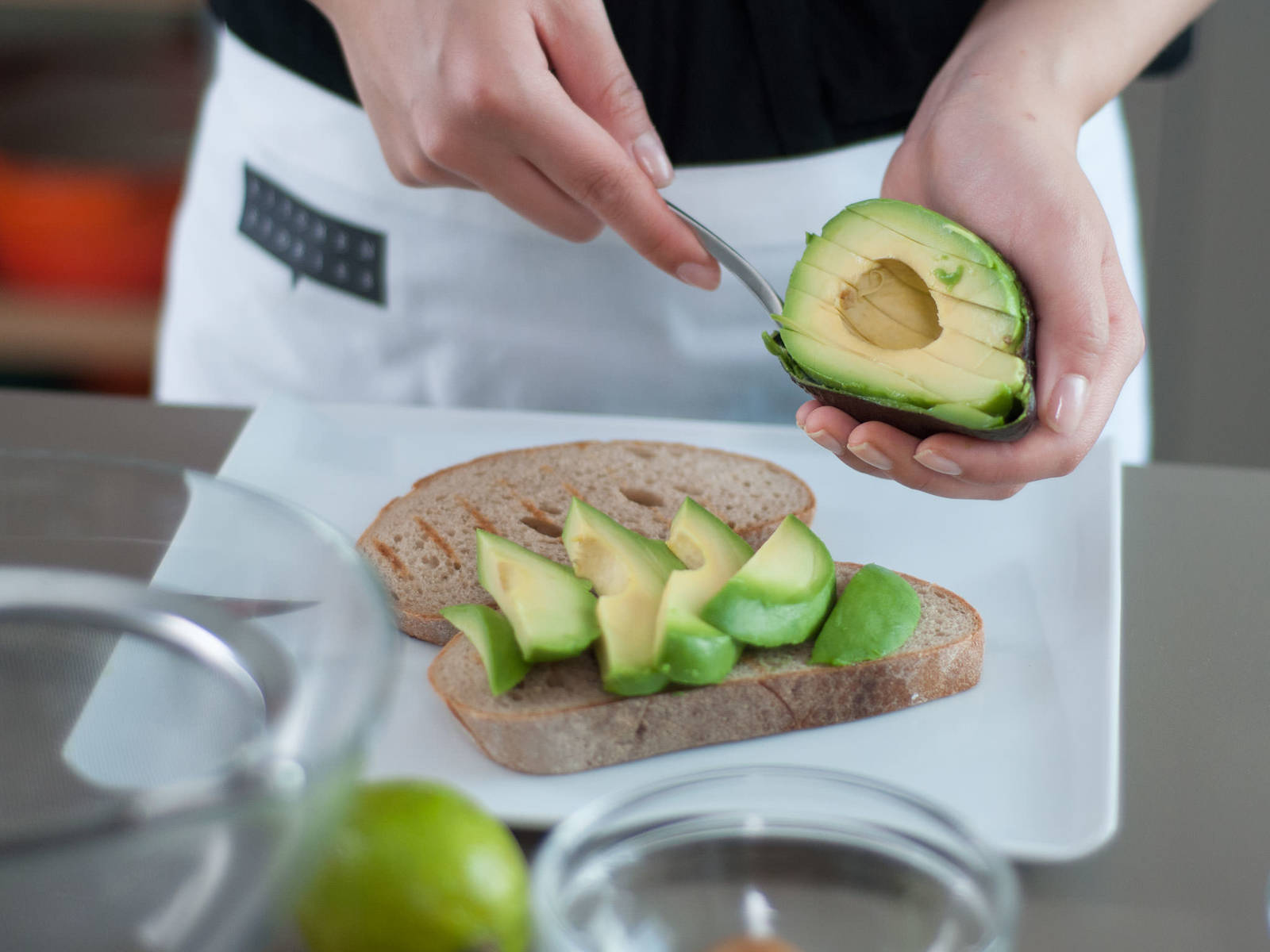 Juice lime. Remove pit from avocado. Slice avocado and layer slices on top of the toast. Season with lime juice, salt, and pepper.