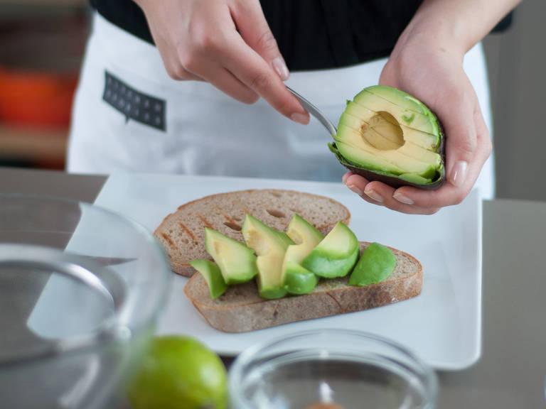 Limette entsaften. Kern der Avocado entfernen. Avocado in Scheiben schneiden und auf dem Brot anrichten. Mit Limettensaft, Salz und Pfeffer würzen.