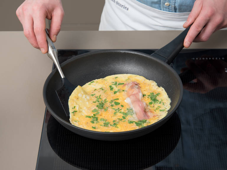 Add cream cheese and a portion of prosciutto to the omelette. Fry for 1 min. more, then fold omelette inside the pan.