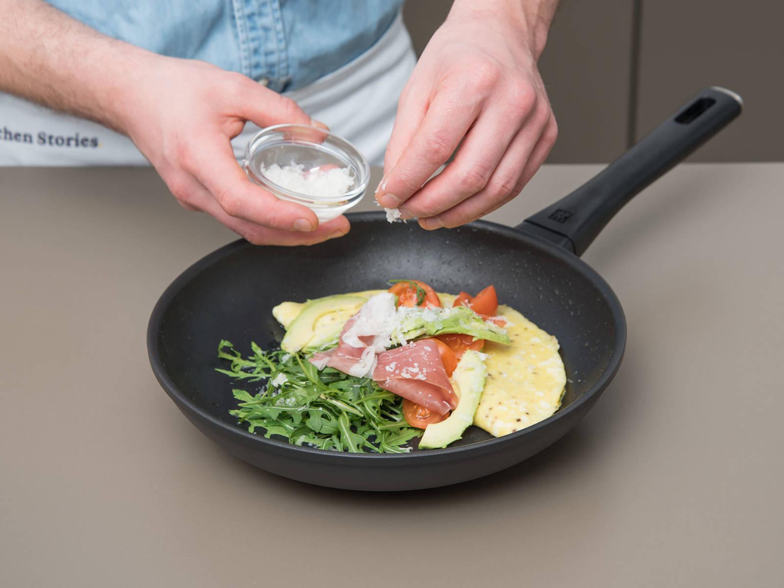 关火取下煎锅。佐以芝麻菜、番茄、熏火腿和牛油果。饰以帕马森干酪屑,趁热享用吧!
