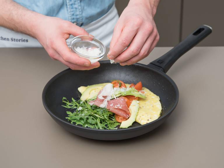 Pfanne vom Herd nehmen. Omelett mit Rucola, Tomaten, dem übrigen Prosciutto und Avocado anrichten. Mit Parmesan garnieren und sofort genießen!