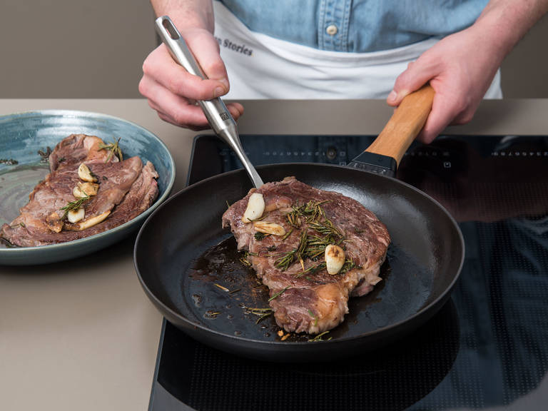 Meanwhile, pre-heat oven to 60°C/120°F. Heat a cast iron pan over medium-high heat. Once pre-heated, remove steaks from freezer bag and transfer them to the pan, together with herbs and garlic. Sear for approx. 4 – 5 min. on both sides. Transfer steaks, herbs, and garlic to a soup plate. Cover with another plate and let rest in the oven at 60°C/120°F for approx. 8 – 10 min.